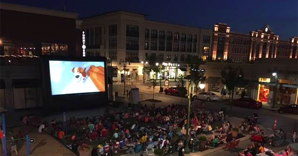 outdoor movie on LED display with crowd in front