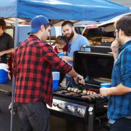 group of people cooking on a grill at an outdoor tailgate event